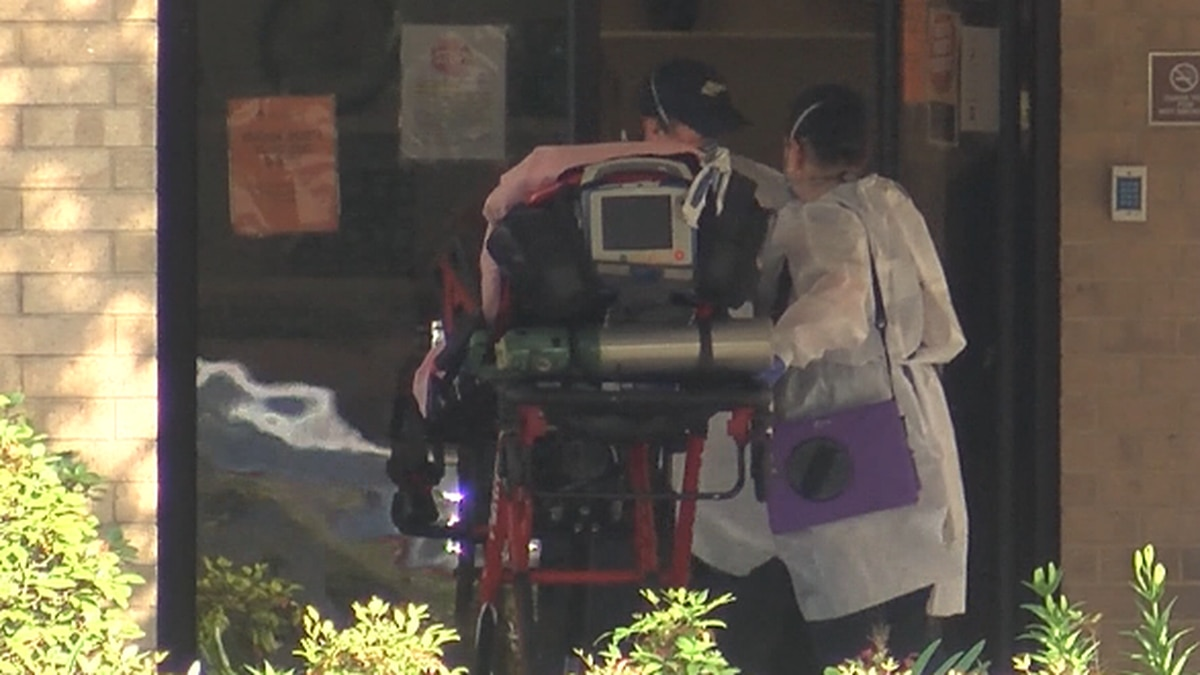 Health care worker pushes an unidentified patient into a facility.