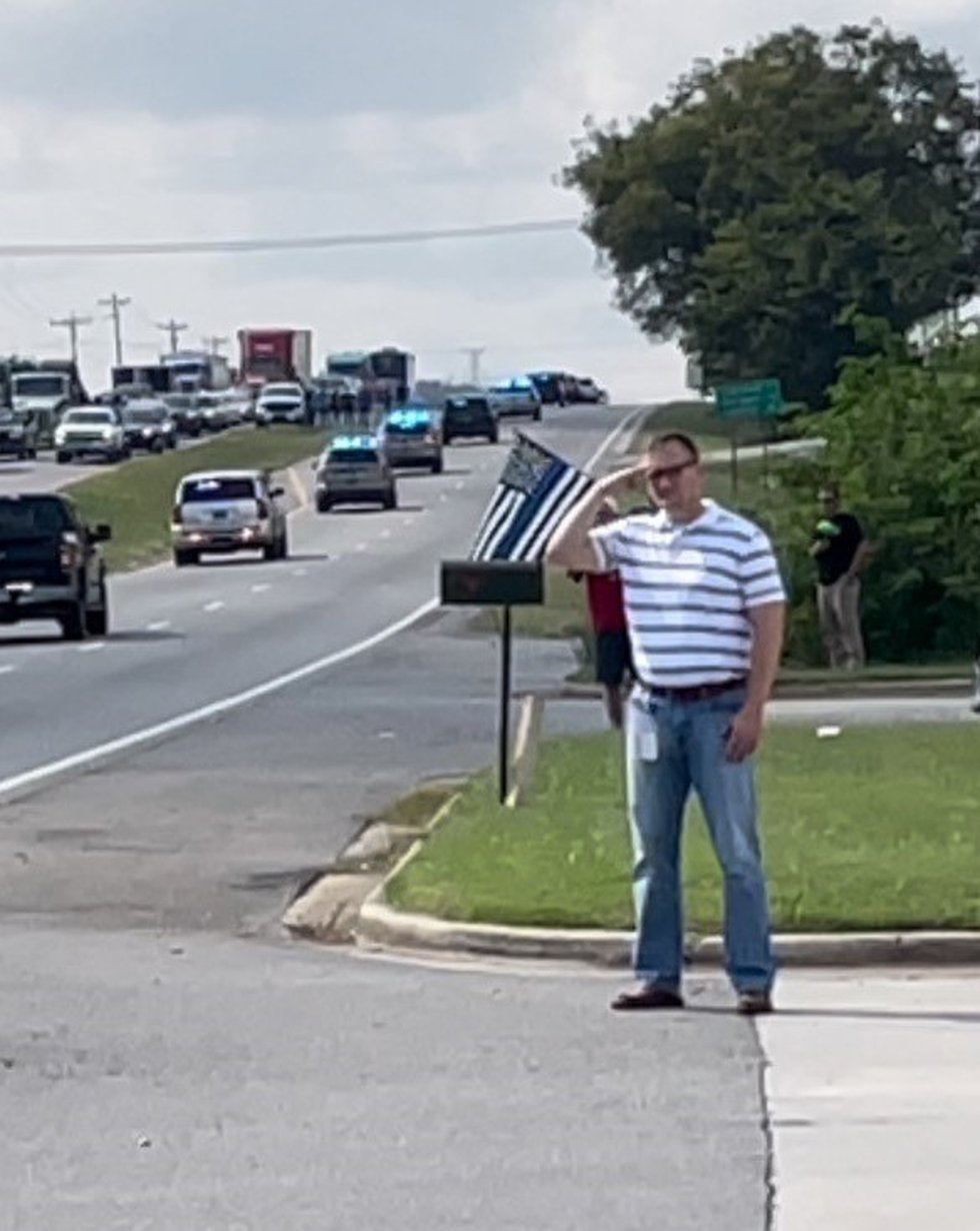 A man saluted the procession of Sgt. Nick Risner as his body was taken back to his home on...