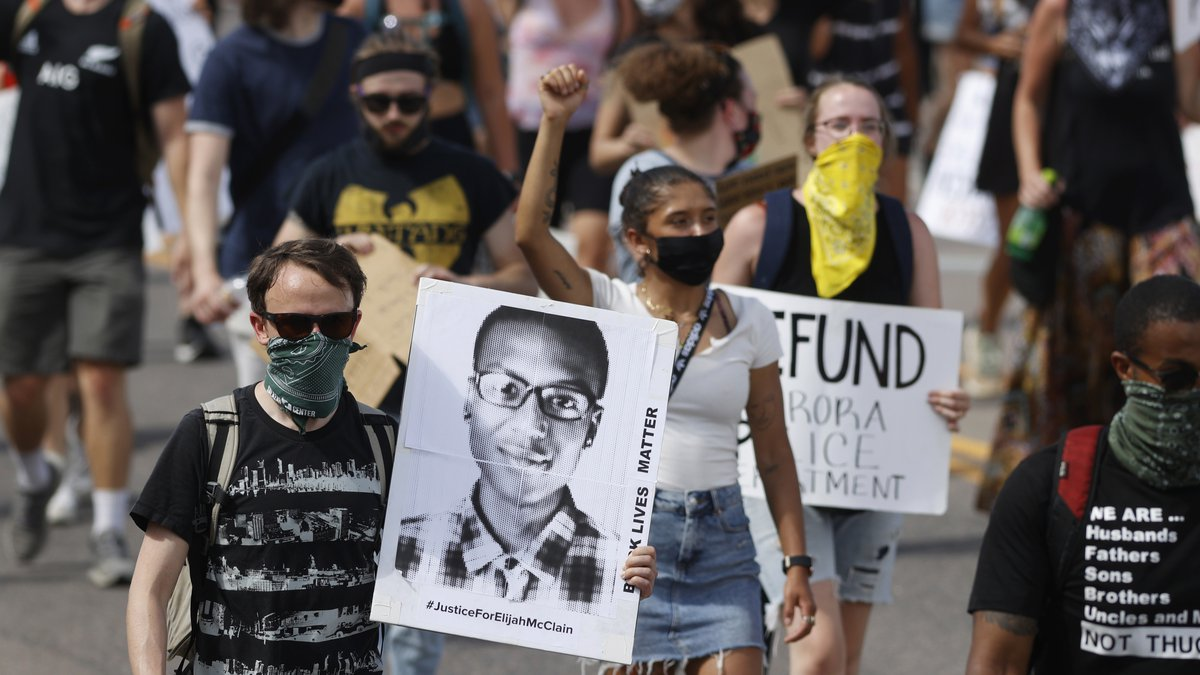 FILE - In this June 27, 2020 file photo, demonstrators carry placards as they walk down Sable...