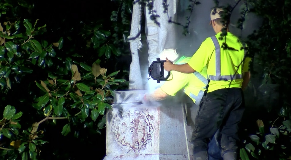 Workers remove the Confederate soldier statue from the Madison County Courthouse