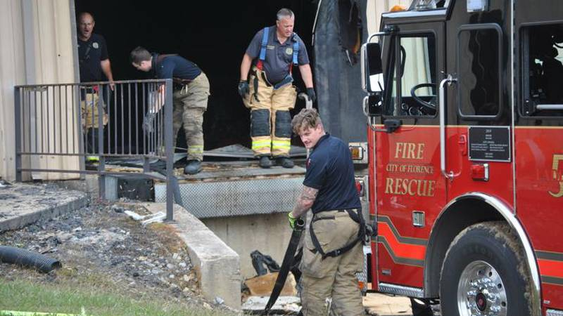 Florence Fire Rescue firefighters remove hoses Monday after putting out hot spots from last...