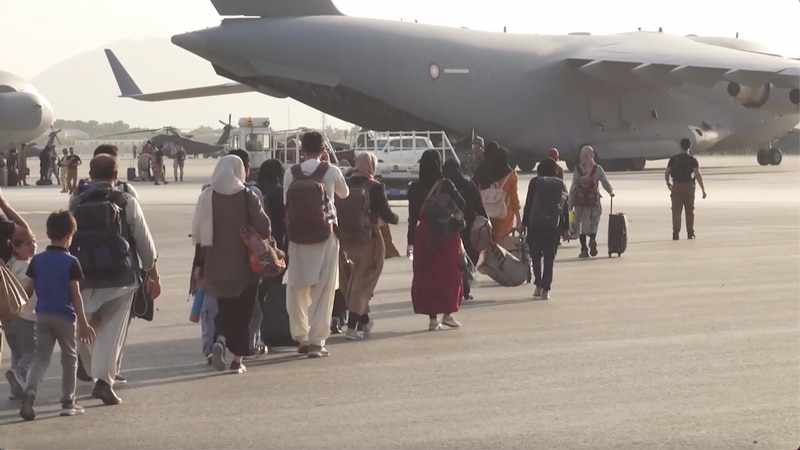 Afghan refugees board planes out of Afghanistan.